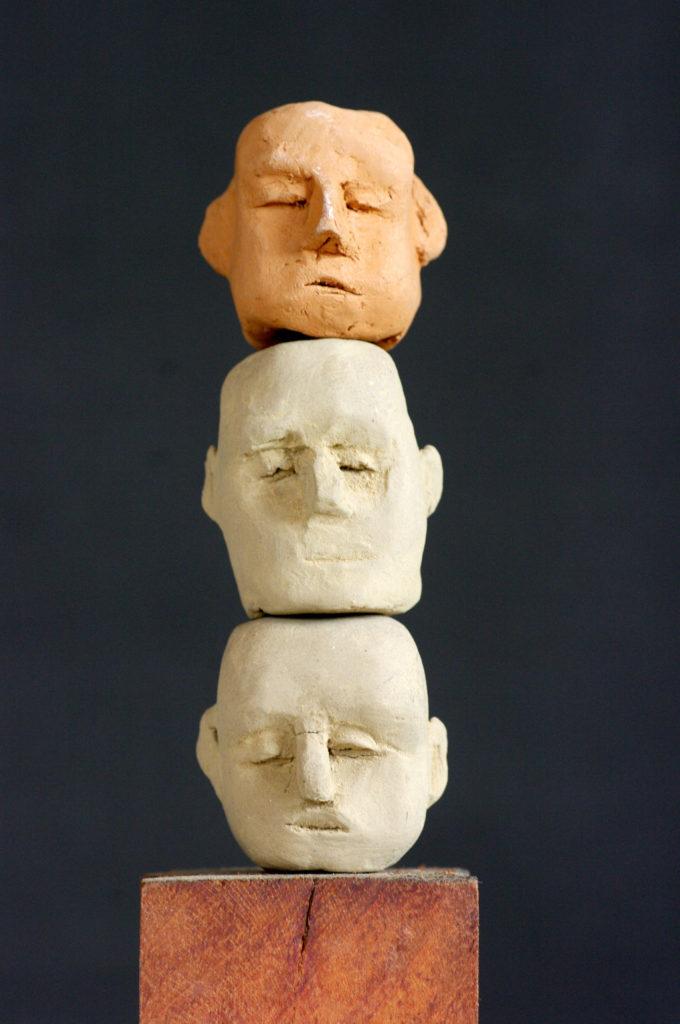 Trois têtes en terre cuite sur socle bois